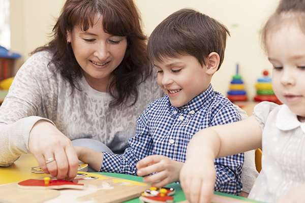 beautiful mature caucasian female teacher collects the puzzle with a pupil,  a boy of preschool age. In the classroom, at the green table.